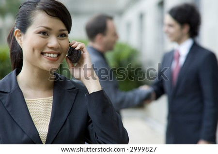 A businesswoman talking on phone with two men meeting in background