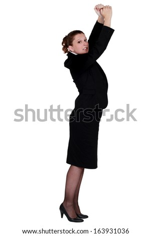 A businesswoman trying to reach something up. - stock photo