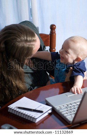 A businesswoman working from home, holding her smiling baby son. - stock photo