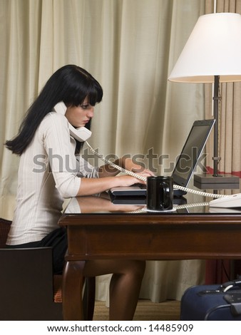 A businesswoman works late into the night on a laptop in her hotel room while on a business trip. - stock photo