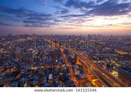 A busy city at dawn and clouds above. - stock photo