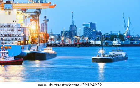 A busy seaport with intense blue saturated color. Boats are on the water, and the city of Rotterdam is viewable in the background. No people. Horizontally framed shot. - stock photo