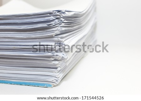 A busy sheets of paper stack on desk isolated. - stock photo