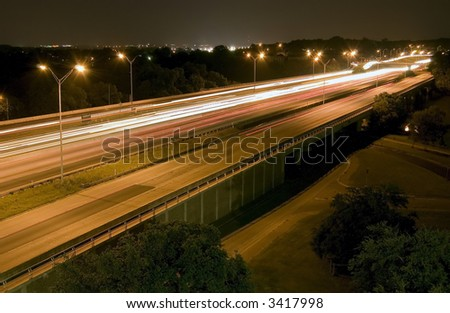 A busy six lane highway taken at night