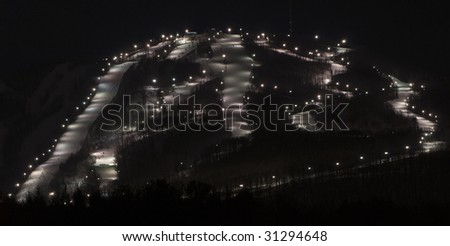 a busy ski mountain at night with many illuminated trails - stock photo