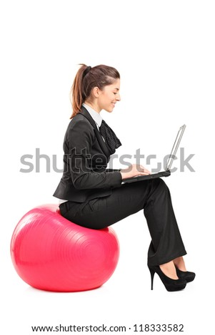A busy woman sitting on a pilates ball and working on a notebook computer isolated against white background - stock photo