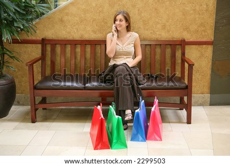 A busy woman taking a rest from shopping and talking on the phone - stock photo
