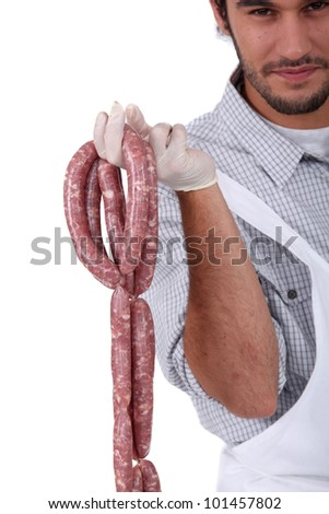 A butcher holding sausages. - stock photo