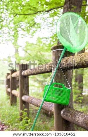 A butterfly net leaning against a wooden post fence. - stock photo