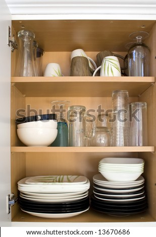 A cabinet full of plates, glasses, and dishes.