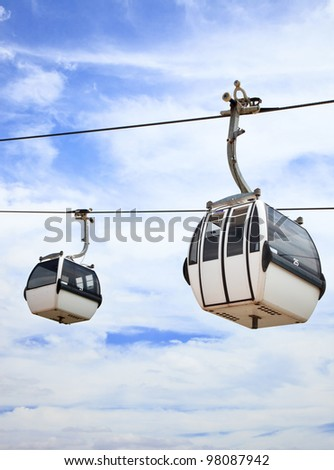 A cablaway with two cable car on a partly cloudy blue sky background