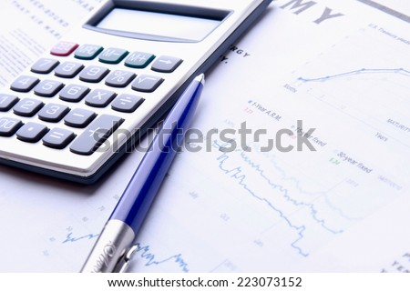 A calculator and a pen over documents - stock photo