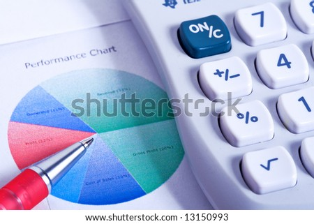 A Calculator and financial figures with pie chart. - stock photo