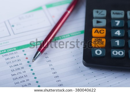 A calculator and pen on financial papers - stock photo