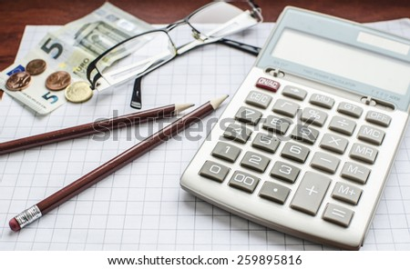 A calculator laying on the office paper with pencils, euro banknotes and coins and transparent glasses  - stock photo