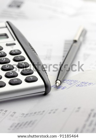 A calculator, pen, and financial statement - stock photo