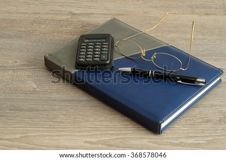 A calculator, pen and reading glasses on top of a note book displayed on a wooden background