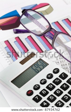 a calculator with graphics of a balance sheet. sales, profit and operating costs. - stock photo