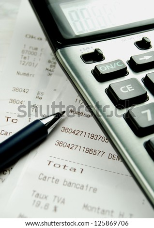 A calculator with till receipts and a pen - stock photo