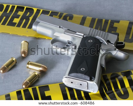 A .45 caliber pistol with bullets, with crime scene tape. - stock photo