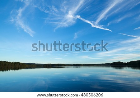 A calm lake in sweden, trails after airplanes in the sky