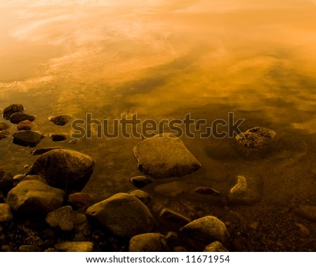 a calm northern lake with some stones in the foreground - stock photo