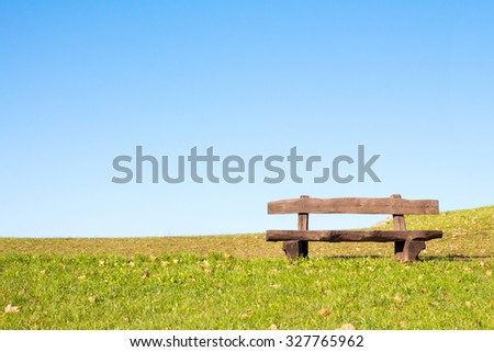 A calm place to rest and relax. An empty wooden bench  over a serene blue sky waiting for a hiker or casual walker to sit and rest. - stock photo