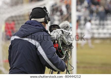 a cameraman filming a football game - stock photo