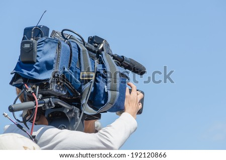 A cameraman is operating a tv camera - stock photo