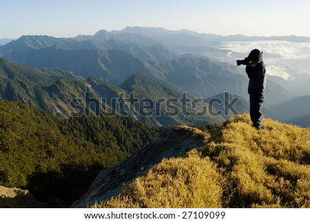 A cameraman standed and shot in the peak. - stock photo