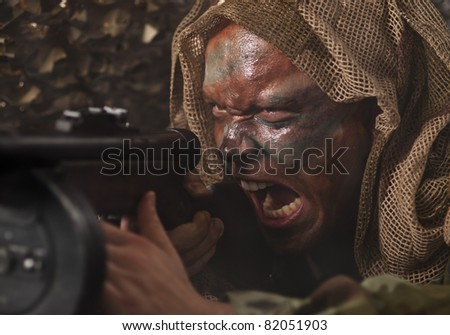 A camouflaged guerrilla soldier screaming while shooting from ambush. - stock photo