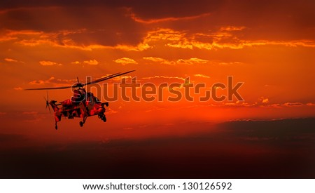A camouflaged military helicopter in flight against a dramatic red sky