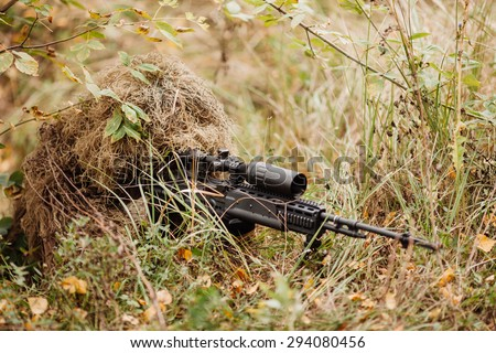 A camouflaged sniper lying in the field aiming through his scope - stock photo