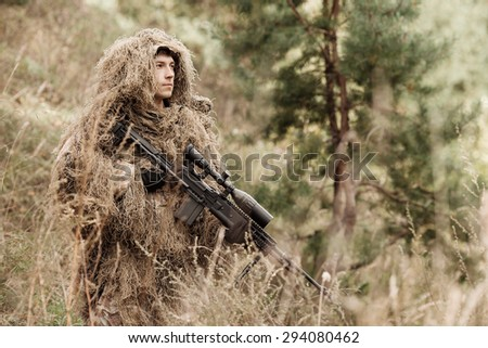 A camouflaged sniper standing in the field and holding his rifle - stock photo