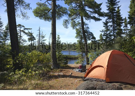 A campsite with an orange tent and cook stove overlook a Boundary Waters lake in northern Minnesota - stock photo