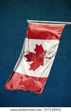 A Canadian flag hanging from a pole blowing in the wind. - stock photo