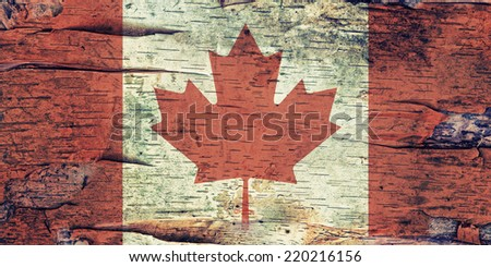 A Canadian flag overlaid on a layer of white paper birch bark creating a grunge image.  White Birch is a tree species native to Canada. Filtered for a retro, vintage look.  - stock photo