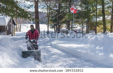 A Canadian man using a snow throwing machine on a winter day after a snowstorm dumped 8 inches of snow.  Man operating a snow blower in Canada. - stock photo