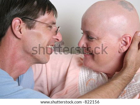 A cancer patient and her husband sharing a tender moment of affection.