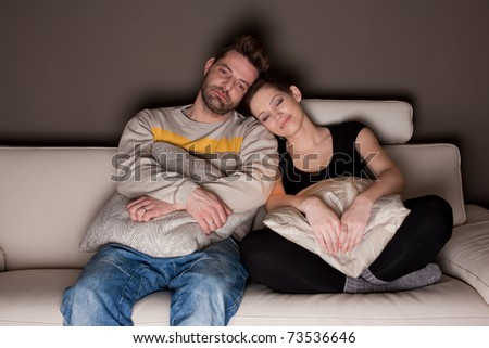 A candid photo of a young couple watching TV - stock photo