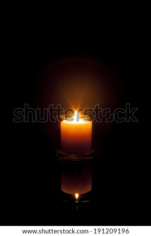 A candle glows in the darkness and reflects off a black surface; warm orange colortones - stock photo