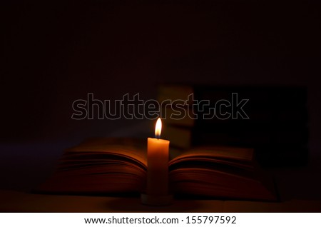 A candle illuminates the open book - stock photo