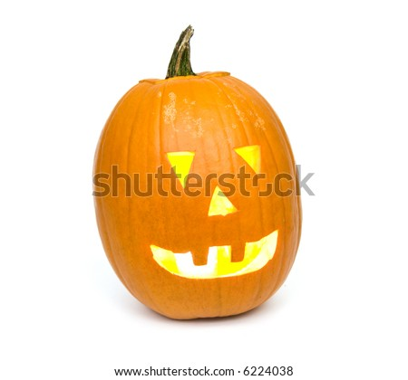A candle lights up the inside of a pumpkin carved for halloween on white background