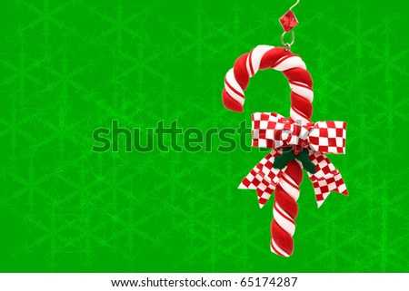 A candy cane hanging on a green snowflake background, Christmas Time