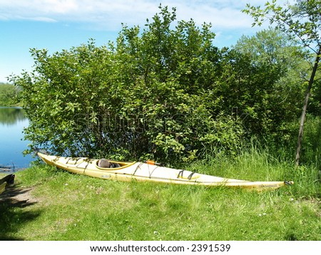 A canoe rests on the green shore of  Ontario lake - stock photo
