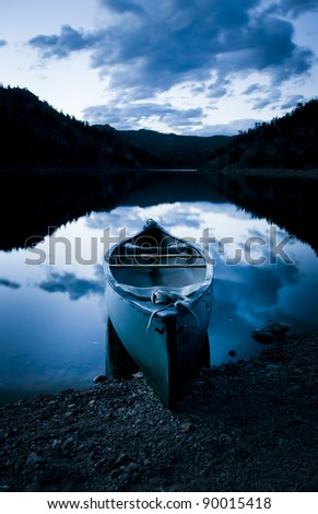 A Canoe sits peacefully on the shores of a placid lake in Colorado - stock photo