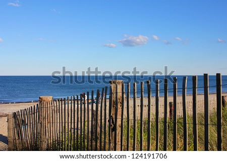 A Cape Cod New England beach lying in the afternoon sun, partly seen through a fence. - stock photo
