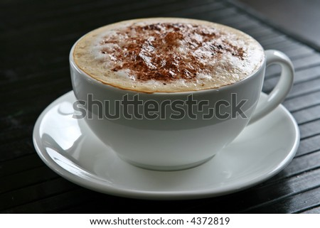 A cappuccino coffee on a saucer with black background.