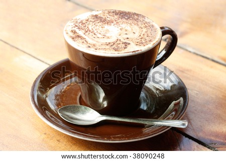 A cappucino on a wooden table - stock photo