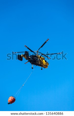 a caption of a black and yellow helicopter with a monsoon bucket on its way to make a drop - stock photo